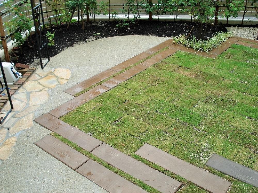 芝生の外周にはコンクリート疑木平板の写真